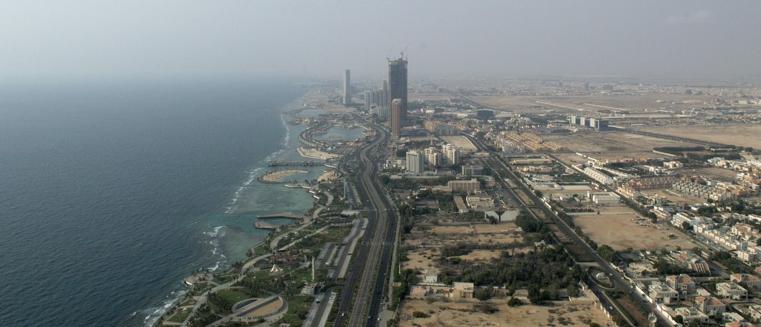 A view down on a beach and a large portion of the Jeddah city from skyscraper