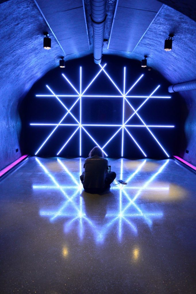 Man sitting in front of a wall with pattern illuminated by LED strips