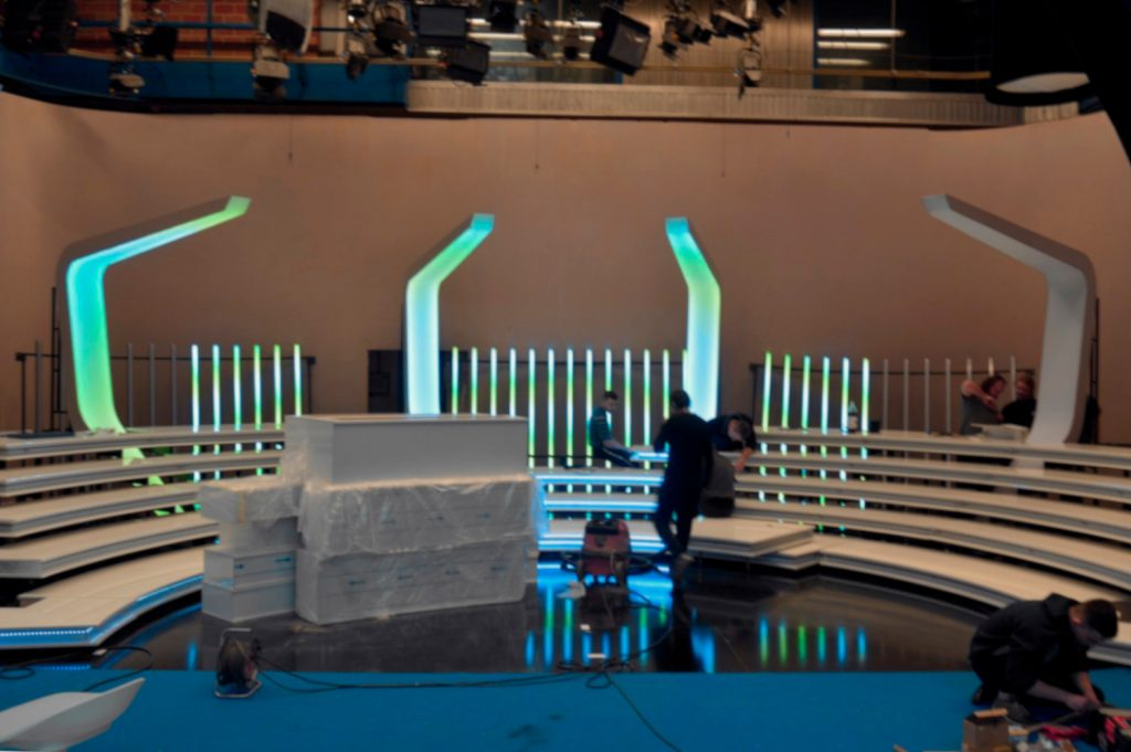 Workers on set in TV studio preparing LED frames and Ribs for installation