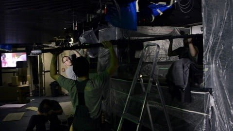 Three workers putting up a metal frame with LED strips and prepare it to be attached to ceiling.