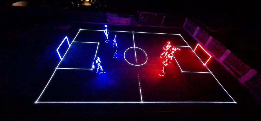 Pitch created with laser, 6 players, each has LED costume, 3 of them Blue, other three RED, illuminated goals on each side of the pitch.